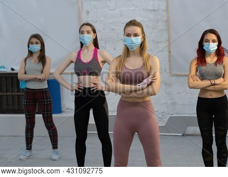 Yoga During Pandemic Wearing Medical Face Protective Mask Athletic Girls In Sports Out Fits Standing