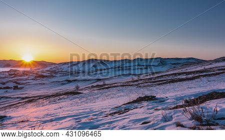 Winter Dawn Over The Siberian Valley. A Mountain Range Against The Sky. The Sun's Rays Paint The Sno