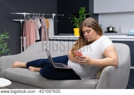 Texting Or Checking On Social Media While Working On Laptop Sitting At Home Curve Body Young Woman S