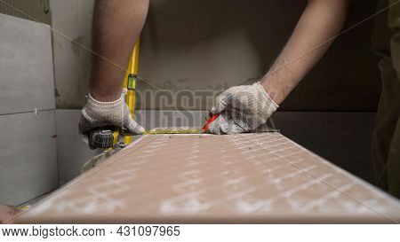 Close Up On Construction Worker Craftsman Using Tool For Cutting Ceramic Tiles For Laying Installati
