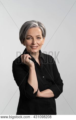 Grey Haired Mid Aged Pretty Woman Looking At Camera With Arms Folded Wearing Black Shirt Isolated On