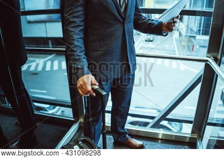 No Face Visible. Businessman Looking At Documents Wearing A Suit Standing Next To The Window With Su