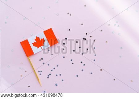 Canada Flag And Sparkles On Pink Background, Flat Lay. Holiday In Canada. 1th Of July, Canada's Happ