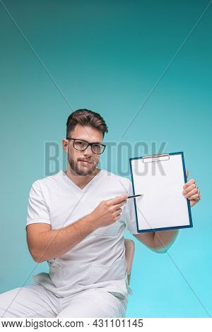 Professional Male Physician Practitioner In Glasses Pointing On Blank Space Sheet. Doctor Report, Di