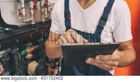 The technician checking the heating system in the boiler room with tablet in hand