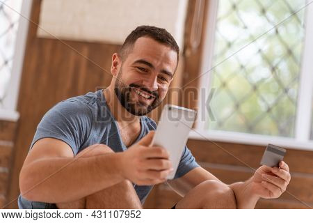 Happy Handsome Bearded Guy With Smartphone And Debit Or Credit Card In Hands Buying Online. Modern D