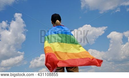 Bisexual, Lesbian, Woman, Transgender Stands With Lgbt Flag Against Blue Sky With Clouds On A Sunny