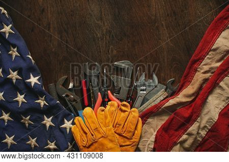 Worn work gloves on tools with US American flag. Made in USA, American workforce, blue collar worker, or Labor Day concept.