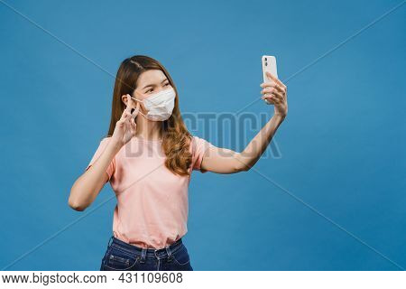 Smiling Adorable Asian Female Wearing Medical Face Mask Making Selfie Photo On Smart Phone With Posi