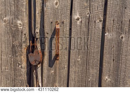 Closed Wooden Door With Lock And Handle. A Barn With A Locked Door. A Rusty Old Padlock On A Backgro