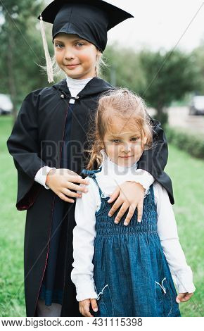 Back To Elementary School Concept. Little Girl Goes To First Grade With Little Sister. Ceremony Of G