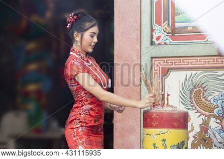 Chinese Woman In A Red Cheongsam Dress Holding Incense Pay Homage To Chinese God At Shrine. Concept