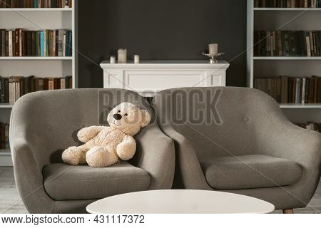 Teddy Sitting On Armchair. Teddy Bear On Grey Chair Next To Empty One In Interior. Beautiful Living