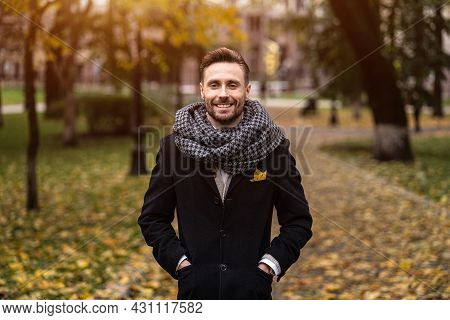 Smiling Handsome Young Man Looking At Camera Standing Outdoors With Hands In Pockets Of His Dark Blu