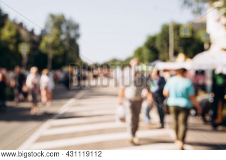 Blurred Background, Defocus People Walk Down Street On Sunny Summer Day. Concept Of Holiday, Event,