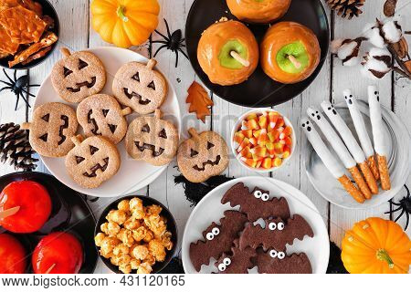 Rustic Halloween Treat Table Scene Over A White Wood Background. Overhead View. Selection Of Candied