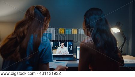 Young Student Asia Ladies Watching Lesson Online And Studying With Roommate Site On Table In Living