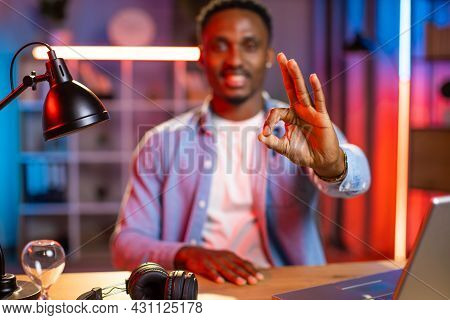 Blurred View Of Handsome Smiling Young African American Guy, Working On Computer In The Evening At H