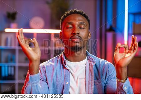 Portrait Of Smiling Relaxed African Man In Denim Shirt Practising Yoga Exercises During Evening Time