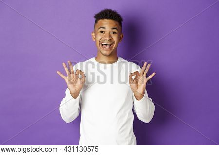 Image Of Satisfied African-american Guy Showing Okay Signs, Being Pleased With Something, Like And A