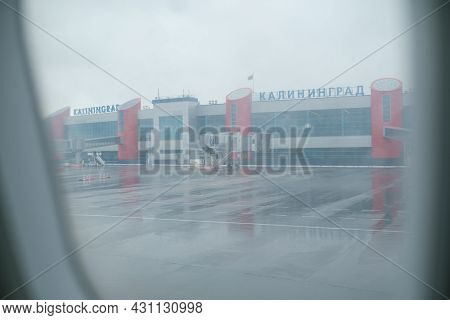 Kaliningrad, Russian Federation - April 25, 2021: Wet airfield and modern building of Kaliningrad airport behind window of aircraft on rainy day