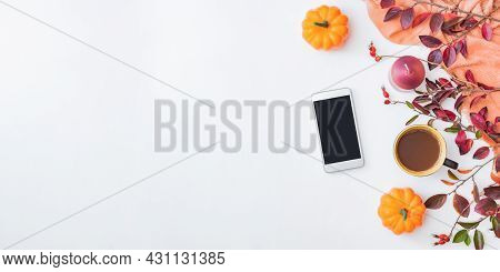 Flat Lay Home Office Desktop With Smartphone, Colorful Autumn Leaves, Scarf And A Cup Of Coffee On A