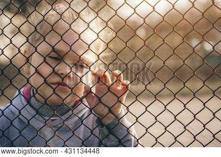 Little Girl With A Sad Look Behind A Metal Fence, Social Problems, Raising Children In Orphanages