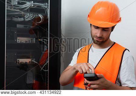 Workman In Helmet Holding Electrical Tester Near Switchboard