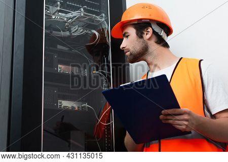 Side View Of Workman In Hard Hat Holding Clipboard Near Switchboard