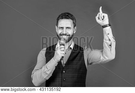 Happy Man With Unshaven Facial Hair Speak Into Microphone Keeping Index Finger Raised, Idea