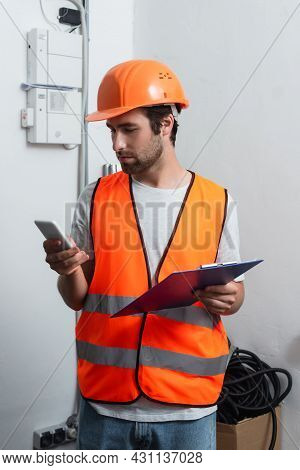 Workman With Smartphone And Clipboard Standing Near Switchboard