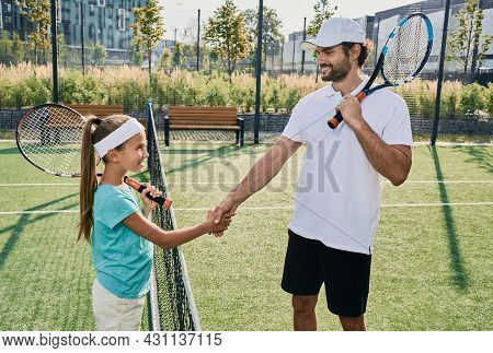 Little Girl Shakes Hands With Her Professional Coach Near Tennis Net Before Playing Tennis. Learning