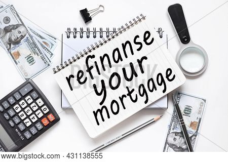 Refinance Your Mortgage. Notebook On White Workspace. Near The Notepad Dollar Bills And A Calculator