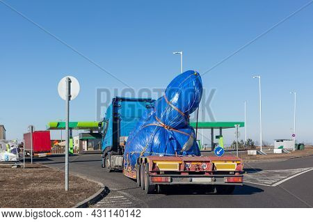 Blue Truck With Special Semi-trailer For Oversized Loads Transportation. Oversize Load On Flatbed Tr