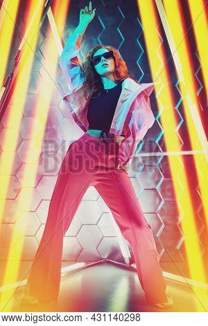 Beautiful young dancer girl dancing in neon light. Modern dances. Disco. Hi-tech dance style.