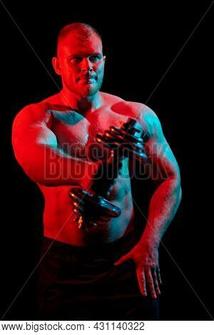 Portrait of a strong handsome athletic man holding a dumbbell in his hand on a black background. Bodybuilding and weightlifting. Studio portrait in mixed colored light.
