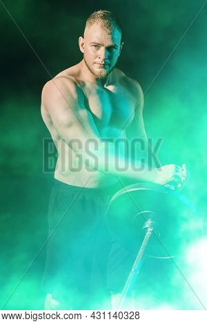 Handsome muscular man doing exercises with a barbell on a dark smoky background. Health and sports concept. Weightlifting.
