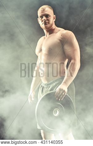 Sports concept: weightlifting, bodybuilding. Portrait of a muscular handsome athletic man holding a large iron disk in his hand. Black background with smoke.