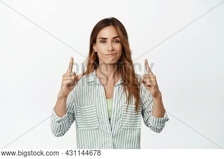 Smug Face. Confident And Ambitious Business Woman Smiling Pleased, Pointing Fingers Up At Top Promo