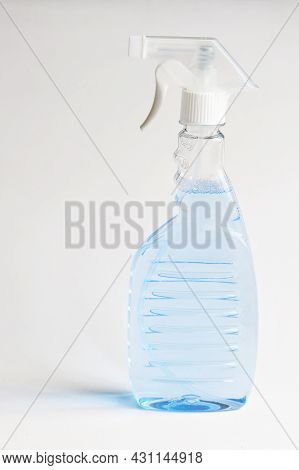 Transparent Container With A Spray Bottle And Light Blue Disinfectant Liquid On A White Background.