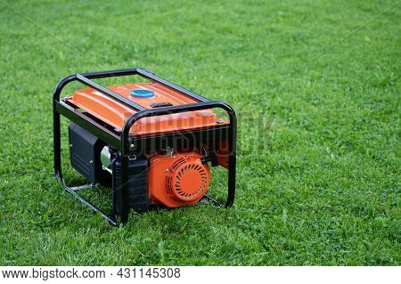 Portable Electric Generator On The Green Grass Outdoors