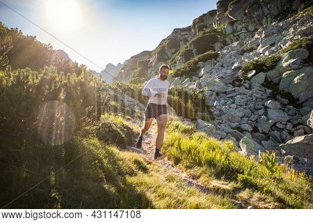trail runner running in mountain landscape at sunset active lifestyle