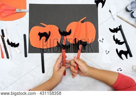 Child Making Pumpkins For The Holiday Of Halloween. Funny Crafts From Paper. Halloween Decor. Handic