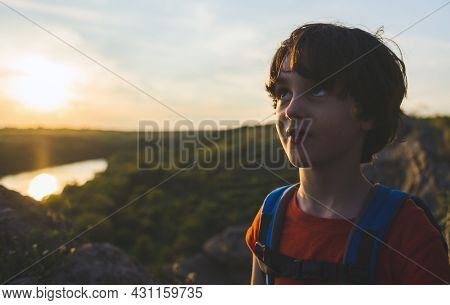 Portrait Of A Boy With A Backpack On The Background Of The Setting Sun, Boy With A Backpack On A Hik