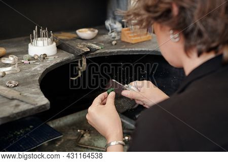 Over shoulder view of craftswoman using polisher while working with jewelry in workshop
