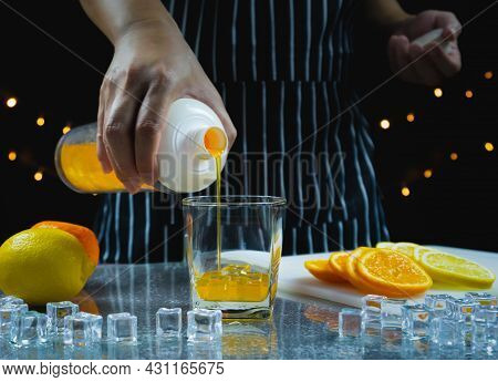 Man Pour Orange Juice In Glass Near Slice Fresh Lemon And Orange On Table, Bartender Prepare Fruit C