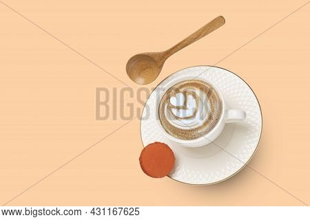 A White Porcelain Cup With Cappuccino Coffee And A Gold Rimmed Saucer With A Wooden Spoon And An Ora