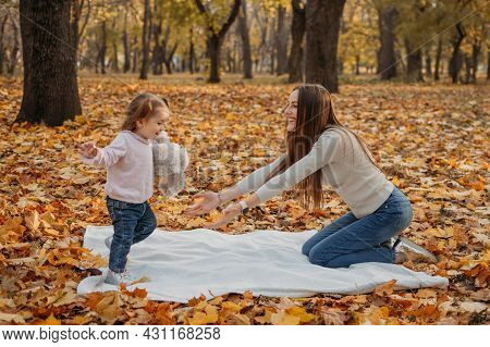Happy Family Mom And Toddler Baby Girl Playing Outdoors In Fall Park. Little Girl And Her Mother In