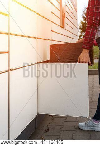 Pickup Parcel. Courier Box In Woman Hands At Post Delivery Automat Terminal. Self Service Post Termi