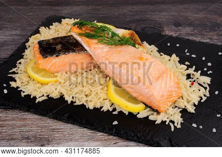 Two Cooked Salmon Fillets With Rice And Dill Herb Garnish On A Slate Serving Board